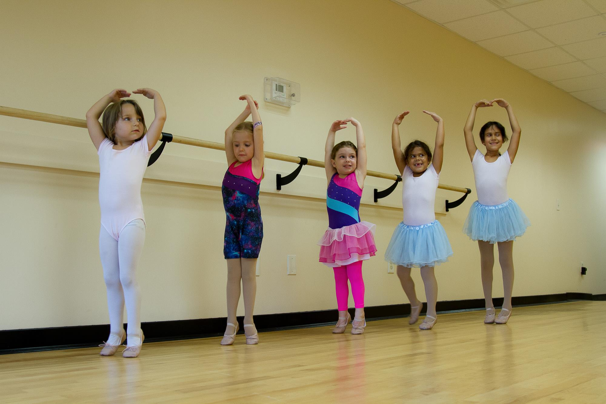 Five girls lined up against wall doing ballet