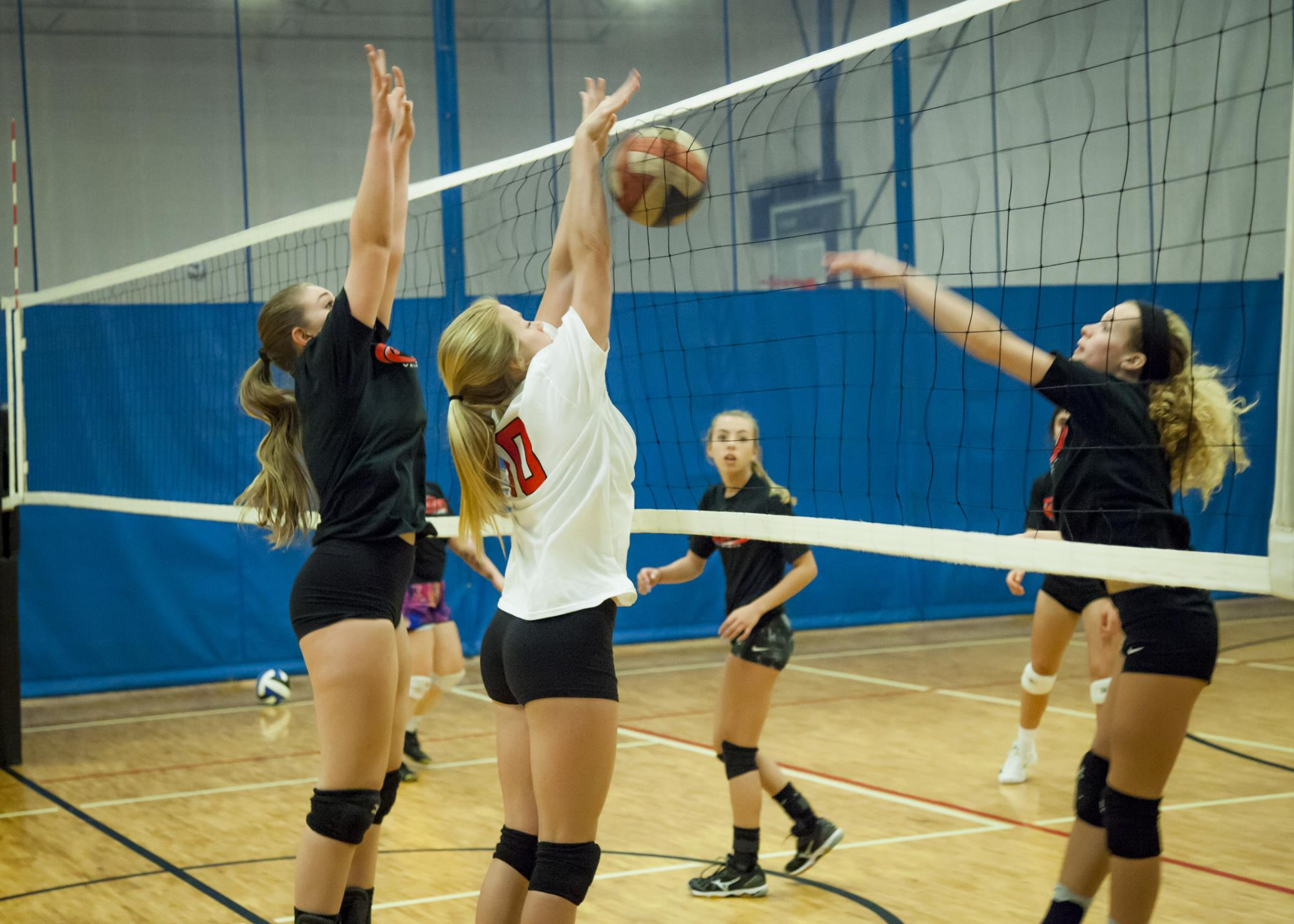 Girls playing volleyball with one girl spiking the ball