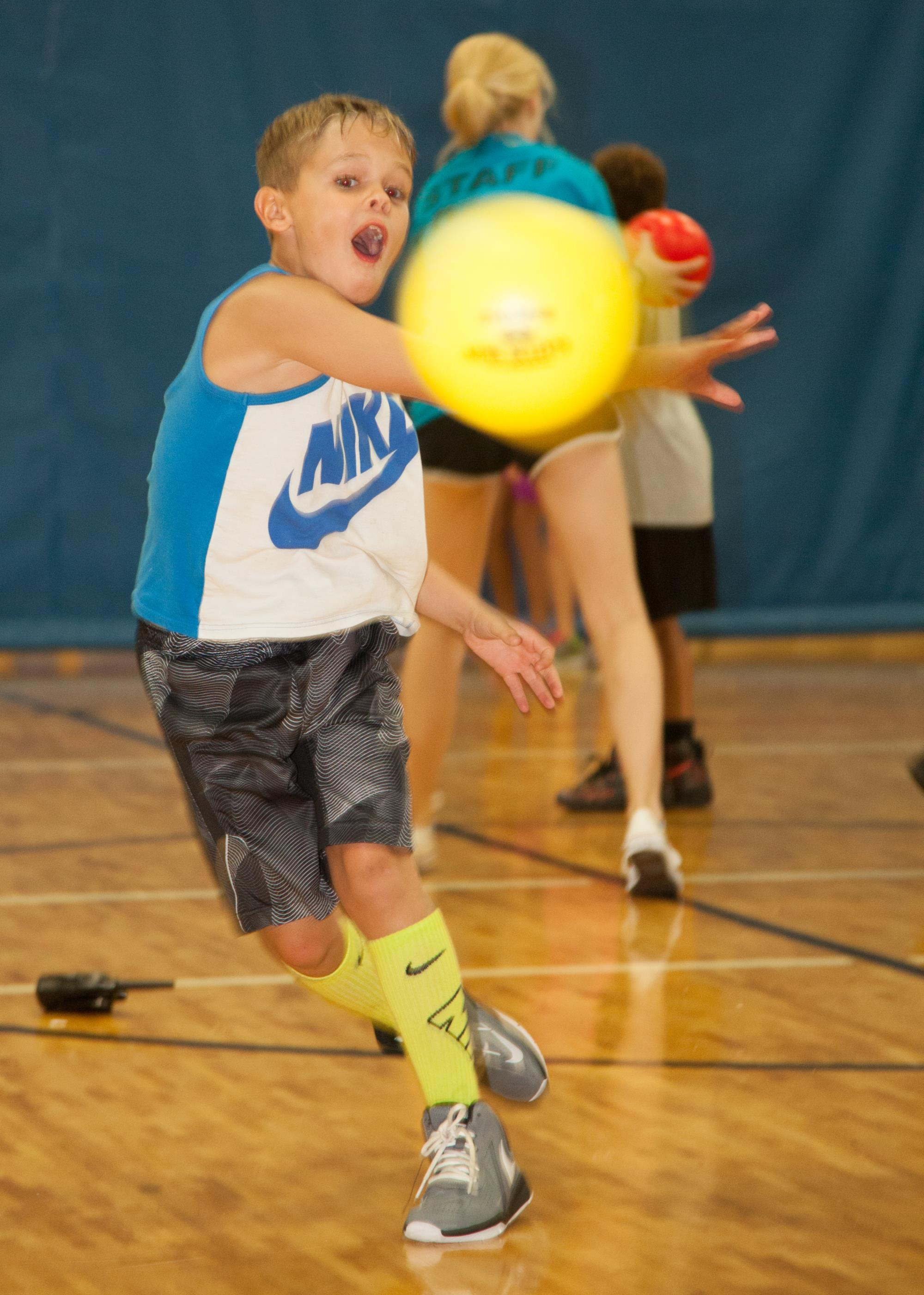 Boy throwing a yellow dodge ball