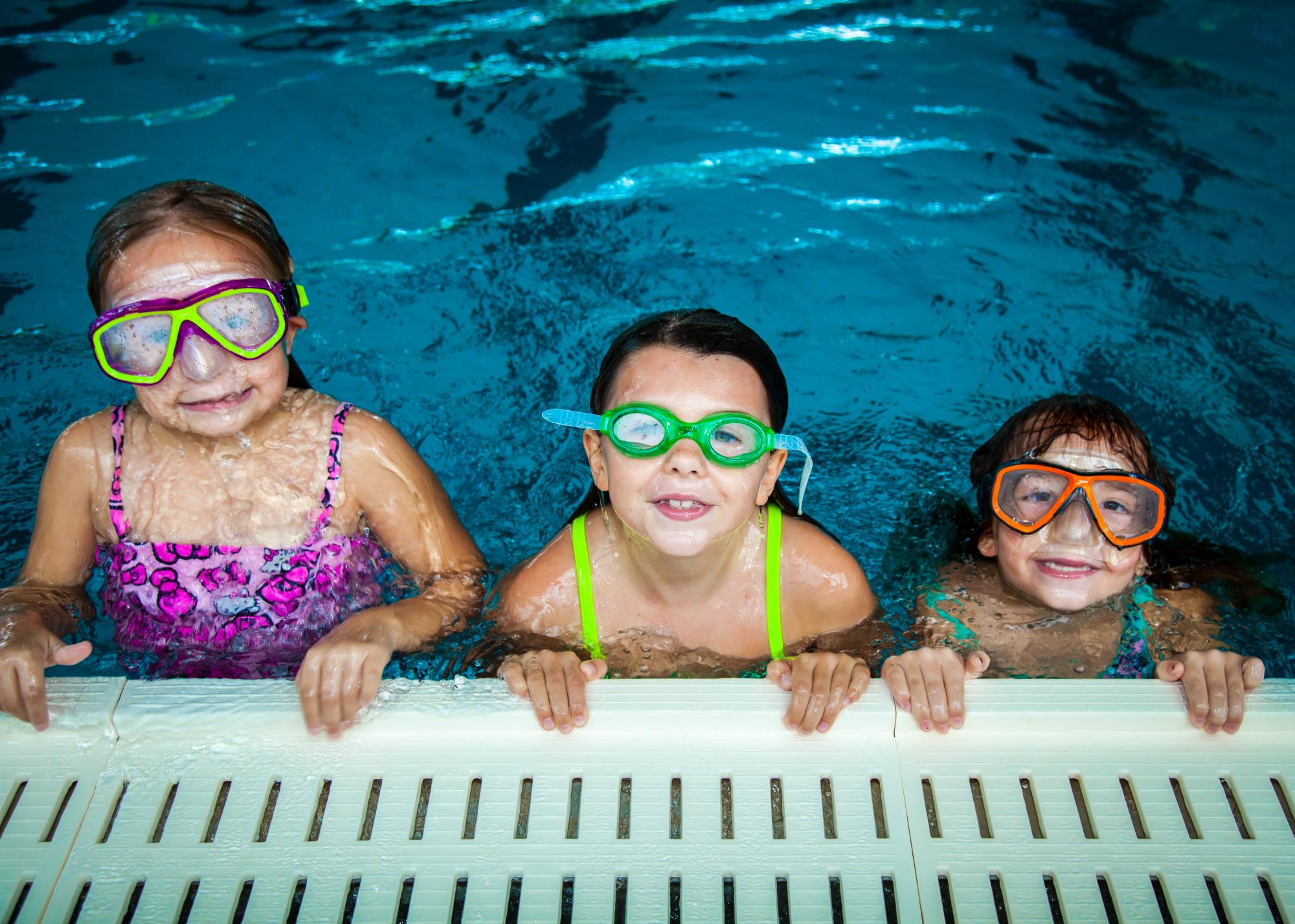 Three girls smiling while holding on to side of pool